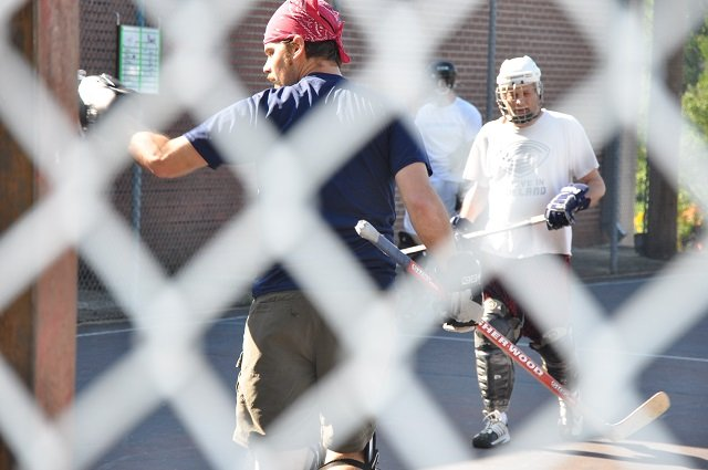 An Atlanta Street Hockey Club Player, as seen through a fence around a court at Bessie Branham Park in Kirkwood. Photo by Dan Whisenhunt