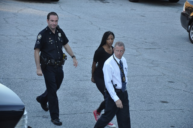 Atlanta Police escort Shanelle Woodard, 22, to a waiting police van on July 16.  Woodard is accused of helping Joseph Alan Lewis conceal evidence in the case of an aggravated assault against a cyclist. Photo by Dan Whisenhunt