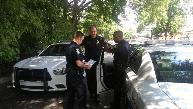 Decatur Police Officers compare notes in the parking lot of Decatur High. File photo by Dan Whisenhunt