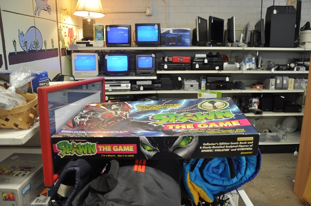 "A board game based on the ""Spawn"" comic book series sits in front of a row of square television sets at Second Life in Avondale Estates. Photo by Dan Whisenhunt"