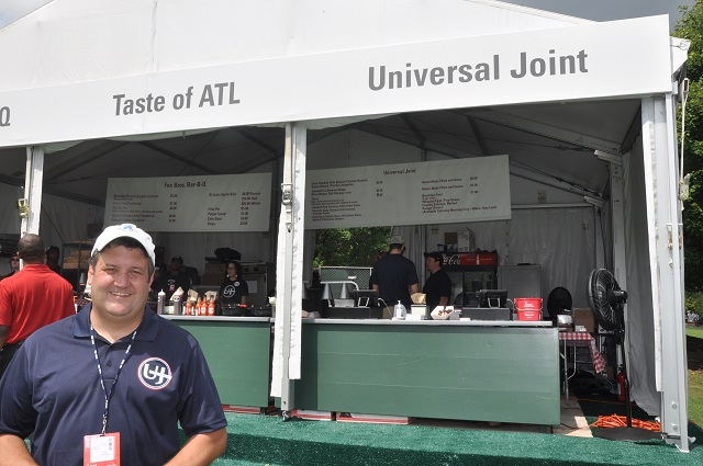 Universal Joint owner Marc Brennan stands in front of the vendor tent at the PGA tour in East Lake.