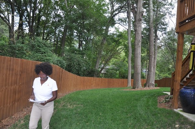 India Woodson, Decatur's new arborist, finishes inspecting a tree at a home in Oakhurst. Photo by Dan Whisenhunt