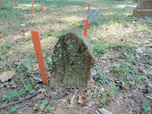 "First marked burial photo: This 1861 stone is believed to be the first marked burial in the cemetery. Digital photography revealed a faint ""RIP"" engraved on the eroded stone. Photo by Dena Mellick"