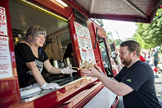 Jennifer Vontillius (left) hands Josh Kalb his corndog at the Pallookaville food truck during the Kirkwood Spring Fling. Photo: Jonathan Phillips