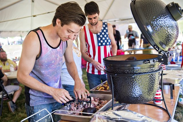 Andrew Desrosiers (left) shreds barbeque that he and Michael LaMont cooked in the barbeque competition during the Kirkwood Spring Fling. Photo: Jonathan Phillips